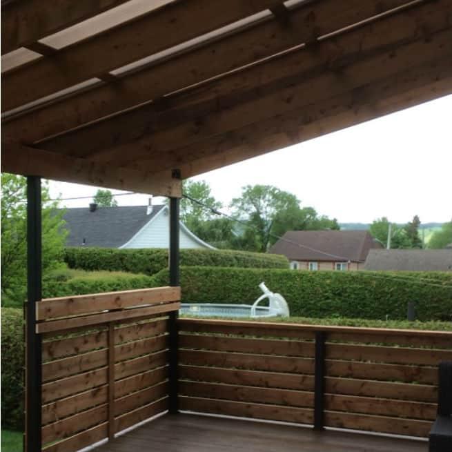 Toit en polycarbonate au-dessus d'un balcon avec rampes en bois
