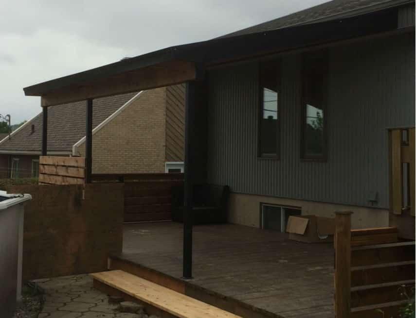 Auvent de balcon avec poteaux en acier noir et rampes en bois